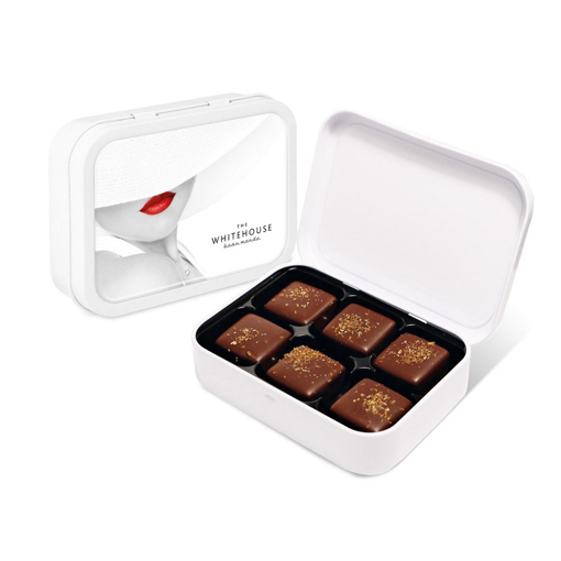 a white branded tin filled with 6 chocolates
