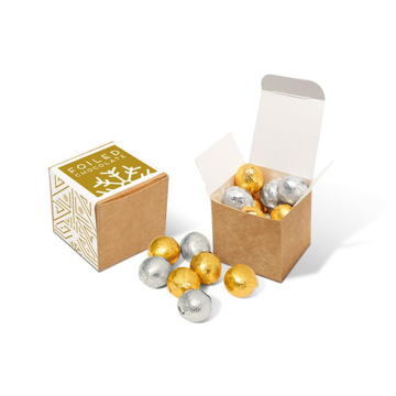 a brown cube filled with silver and gold chocolate balls with promotional festive label.